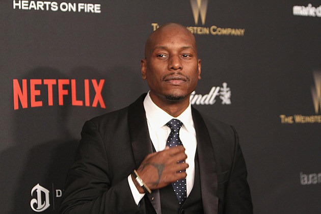 tyrese gibson holding tie in black suit